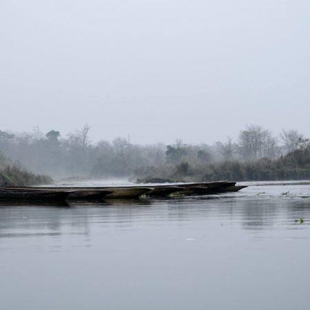 Boats in Rapti river in foggy day inside Chitwan National Park, Nepal