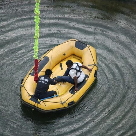 Man being untied from bungee cord in raft after bungee jumping in Hemja, Pokhara, Nepal