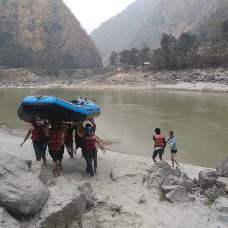 Rafters carrying raft in riverside during White Water Rafting in Trishuli River