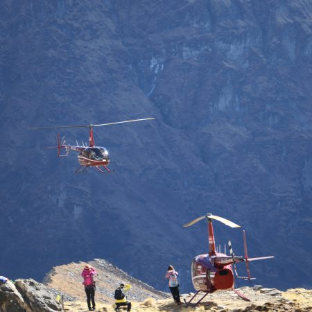 People taking pictures of helicopter arriving at Annapurna Base Camp