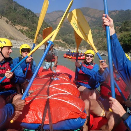 Rafters lifting paddles during White Water Rafting in Lower Seti River